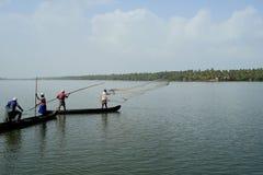 小船的渔夫通过投掷网抓鱼对死水在一个有薄雾的早晨 库存图片