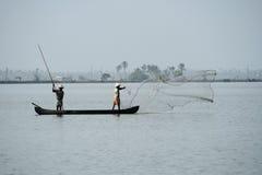小船的渔夫通过投掷网抓鱼对死水 免版税库存图片