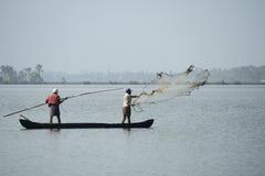 小船的渔夫通过投掷网抓鱼对死水 免版税库存照片