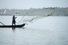 小船的渔夫通过投掷网抓鱼对死水 库存图片