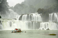 小船的游人接近板约瀑布,越南 库存照片