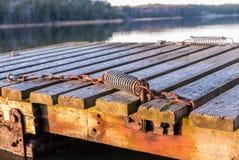 小船的老生锈的停泊春天设备在木码头 免版税库存照片