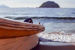 小船的边在海湾和海岛的背景的 库存照片