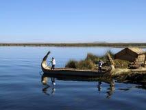 小船的Uro男孩, Uros浮动海岛 免版税库存图片