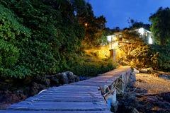 小船码头和小屋在晚上 免版税库存图片