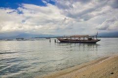 小船美丽的景色在蓝色海热带海滩的与多云天空,Gili Trawangan,龙目岛,印度尼西亚 库存图片