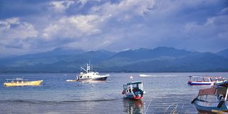 小船美丽的景色在蓝色海热带海滩的与多云天空,Gili Trawangan,龙目岛,印度尼西亚 库存照片
