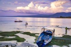 小船美丽的景色在蓝色海热带海滩的与多云天空,Gili Trawangan,龙目岛,印度尼西亚 免版税库存图片