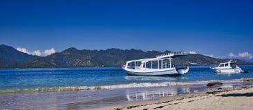 小船美丽的景色在蓝色海热带海滩的与山在背景,Gili Trawangan,龙目岛,印度尼西亚中 库存图片