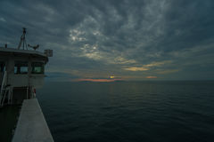 小船航行在美好的日落期间的多云风暴日 免版税库存照片