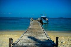 小船被停泊在有蓝色海和天空的跳船 免版税库存照片