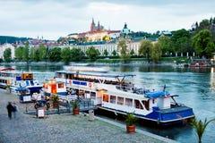 小船被停泊对河伏尔塔瓦河的河岸在布拉格。 免版税库存照片