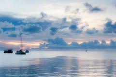 小船软的焦点在黑暗的云彩中的海在日落 免版税库存图片