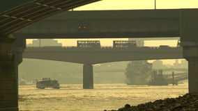 小船通过在铁路桥下的,通过在伦敦桥的公共汽车 股票录像