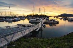 小船靠了码头在游艇俱乐部有美好的日落背景 免版税图库摄影