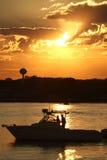 小船风帆通过在日落期间的港口 库存图片