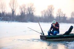 小船饮用的茶的人,当钓鱼鱼在冬天时 免版税库存照片