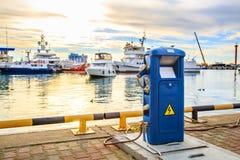 小船,充电船的电子出口的充电站在港口 在口岸靠码头的豪华游艇在日落 免版税库存图片
