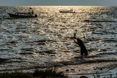 小船&渔夫黄昏光的,湖Atitlan,Guatema 免版税图库摄影