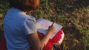 小艺术家女孩画在册页花的铅笔坐草 股票录像