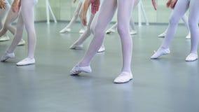 小芭蕾舞女演员小组的特写镜头腿在实践在芭蕾的白色鞋子的教育慢动作 免版税库存照片