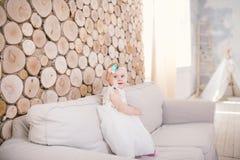小蓝眼睛的女孩白肤金发在有装饰的一件白色薄纱礼服在她的使用和高兴在一个米黄沙发的头在屋子w里 库存图片