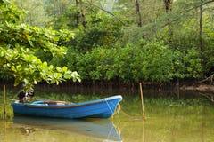 小蓝色小船在一条小运河停放了在美洲红树前面 图库摄影