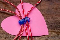 小蓝色心脏和星在红色和白面包师缠绕与桃红色纸心脏 库存图片