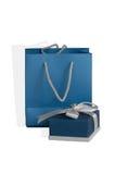 小蓝色框栓与银色丝带和礼物纸袋作为集合 库存图片