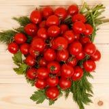 小蕃茄和新鲜的草本在木背景 免版税库存图片
