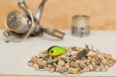 小蟑螂和金属在背景中捞出说谎在小卵石小山,瞬间卷 钓鱼的项目 11/05/2016 图库摄影