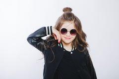 小行家女孩画象太阳镜的 摆在 卷曲现代发型 免版税库存照片