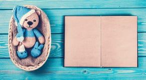 小被编织的玩具熊和一本开放书与空的页 一头软的小熊在篮子 免版税库存照片