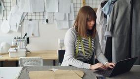 小裁缝` s商店年轻女性店主与膝上型计算机一起使用在她的工作场所 她为新指令织品 股票录像