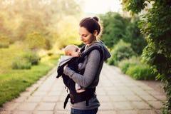 小走外面在日落期间的女婴和她的母亲 M 免版税库存图片