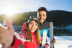 小轿车滑雪和采取Selfie照片冬天雪山混合种族人妇女的雪板手段 库存图片