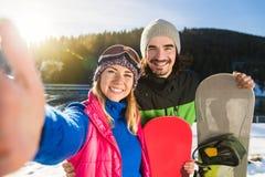 小轿车滑雪和采取Selfie照片冬天雪山里人妇女的雪板手段 库存图片