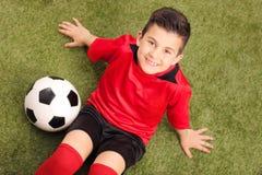 小辈足球运动员坐一个绿色领域 库存图片