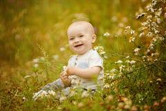 小迷人的小孩男孩光T恤杉在与da的一个领域坐 免版税库存照片