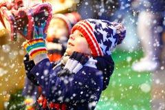 小逗人喜爱的从一个cancy立场的孩子男孩买的甜点在圣诞节市场上 免版税图库摄影