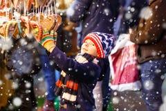 小逗人喜爱的从一个cancy立场的孩子男孩买的甜点在圣诞节市场上 免版税库存照片
