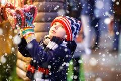 小逗人喜爱的从一个cancy立场的孩子男孩买的甜点在圣诞节市场上 免版税库存图片