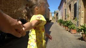 小逗人喜爱的冒险的女孩主导的父母在一个老欧洲镇 股票录像