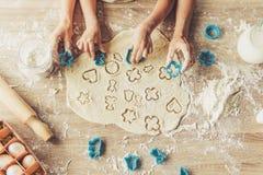小逗人喜爱的准备曲奇饼的女孩和她的母亲 免版税库存照片