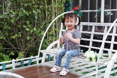 小逗人喜爱的可爱的女孩中国儿童微笑和戏剧坐白色长凳举行棒棒糖和花在夏天公园自然 免版税图库摄影