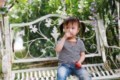 小逗人喜爱的可爱的女孩中国儿童微笑和戏剧坐白色长凳举行红色爱形状泡沫在夏天公园自然 免版税库存照片