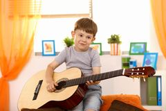 小逗人喜爱的吉他的孩子 库存图片