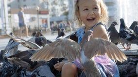 小逗人喜爱的女孩哺养的街道鸽子特写镜头画象在公园 免版税库存图片