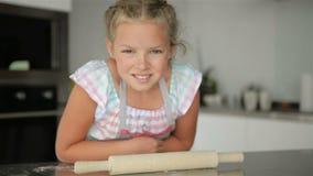 小逗人喜爱的女孩在厨房烹调 获得乐趣,当做蛋糕和曲奇饼时 微笑和查看照相机 股票录像