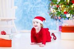 小逗人喜爱的女孩在圣诞树下 免版税库存照片